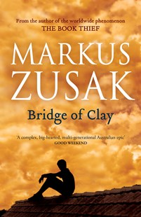 Cover of the book Bridge of Clay by Markus Zusak featuring the silhouette of a boy sitting on a roof and behind him is an orange sky. Image is to accompany the book review on the same page.