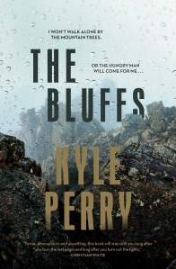 Cover of the book The Bluffs by author Kyle Perry to accompany the book review by The Reading Edit on the same page. Cover image features a rocky outcrop with a misty, rainy sky.